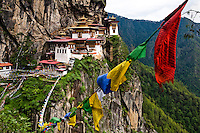 Prayer flags lead towards Taktsang Temple, also known as The Tiger's Nest Temple, a prominent Buddhist temple complex located in the cliffside of the upper Paro Valley.