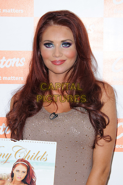 Amy Childs.Former TOWIE star meets the fans and signs copies of her Official 2012 Calendar at Clintons, Bluewater shopping center, Kent, England, .12th November 2012..half length   brown beige  top t-shirt   cheeks blusher make-up .CAP/CJ.©Chris Joseph/Capital Pictures.