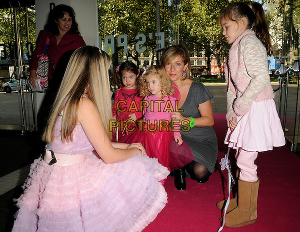"TRACY-ANN OBERMAN & daughter ANOUSHKA INDIA COWAN.At the ""Barbie and the Three Musketeers"" VIP Premiere, Odeon Leicester square, London, England, UK,.September 27th 2009..3 full half length family child kid grey gray dress pink  mother mum mom meeting Barbie kneeling down kids children girls neon green wrist watch  black and white polka dot print  .CAP/CAN.©Can Nguyen/Capital Pictures"
