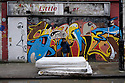 London, UK. 04.04.2015. Small boy walking past abandoned mattresses, East London. Photograph © Jane Hobson.