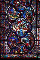 Medieval stained glass Window of the Gothic Cathedral of Chartres, France - dedicated to St John The Evangelist. Bottom panel - Flight into Egypt . Above left - Armourers making shields and saddles, above right - Armourers making stirrups. Central panel - Death of Satheus, above left - John's journey into exile on Patmos, above right - St John on Patmos. A UNESCO World Heritage Site..