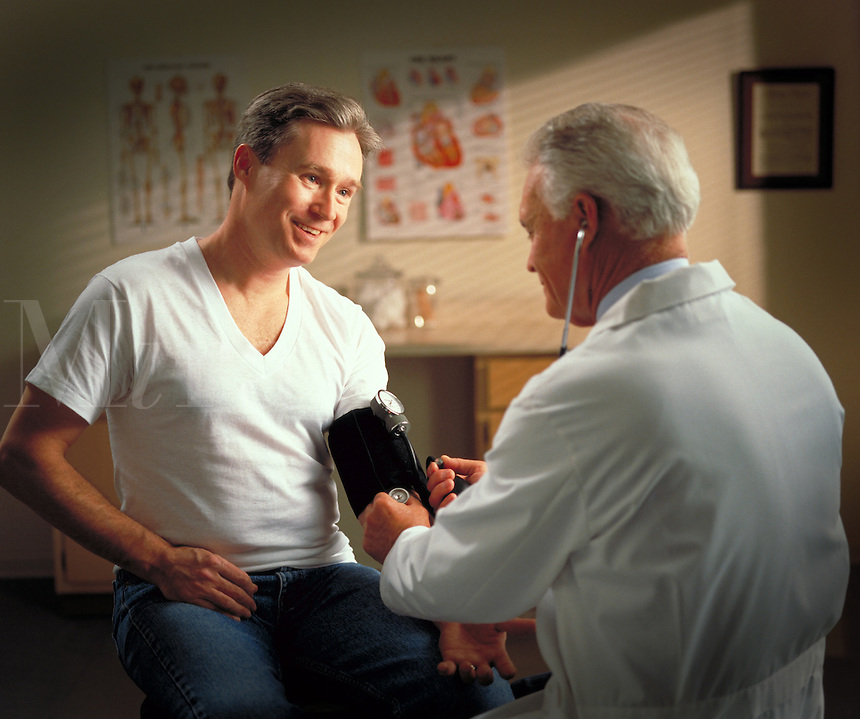 Male doctor taking the blood pressure of a male patient Billboard and broadcast must be negotiated, due to talent agreement. Doctor and patient. United States.