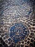 Manhole cover in a cobble street, Ravenna, Italy