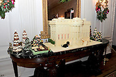 The traditional White House ginger bread house is displayed on the eagle-pedstal side table of the State Dining Room in Washington, DC.  It weighs approximately 400 pounds and took almost 2 months to make. It is an accurate replica of the White House.  The theme for the White House Christmas 2011 is Shine, Give, Share - celebrating the countless ways we can lift up those around us, put our best self forward in the spirit of the season, spend time with friends and family, celebrate the joy of giving to others, and share our blessings with all.  The theme translates to the holiday décor on several levels. There is the literal translation through the use of shiny elements – star motifs, quartz and metallics like copper, aluminum and mirrored paper. There is also a conceptual connection – we're inviting visitors to give their thanks to members of our military, and have once again invited guest artists to share their talents working with the White House. This year's décor also includes handmade decorations crafted from simple materials – paper, felt, and even recycled cans. These are projects that anyone can do at home using readily available materials that are inexpensive or free..Credit: Ron Sachs / CNP