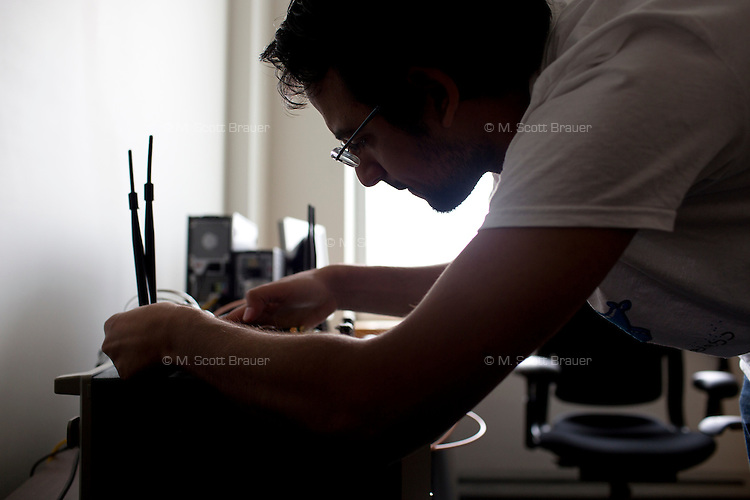 Grad student Ezzeldin Hamed readies software radios used in research in the Wireless Center at MIT in Cambridge, Massachusetts, USA.  Hamed works in Professor Dina Katabi's research group in CSAIL.