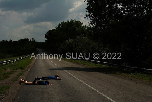 Amvrosiyivka, Ukraine.July 27, 2005 ..Children dry off from a swim in the lake by laying on the hot road......