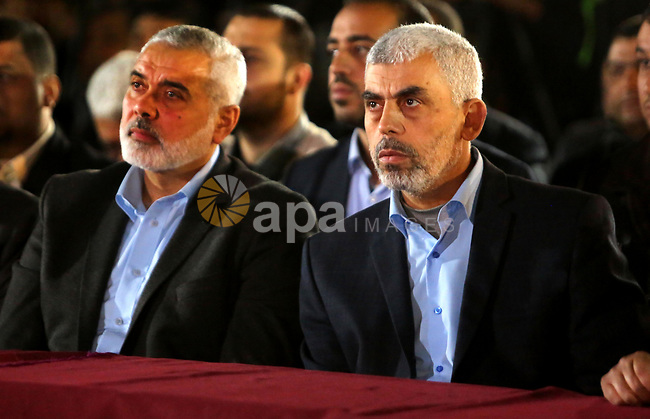 Yahya Sinwar, the new leader of Hamas in the Gaza Strip and senior political leaders of the Islamist movement, Ismail Haniyeh attend a memorial service of Hamas official, Mazen Faqha, who was shot dead by unknown gunmen, in Gaza city on March 27, 2017. Photo by Ashraf Amra