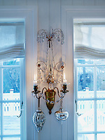 A crystal sconce in the dining room is lit with real candles and decorated with Christmas baubles