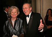 United States Secretary of Defense Donald Rumsfeld and Joyce Rumsfeld joke with photographers before the entertainment at a White House State Dinner for the nation's governors in Washington, DC on February 26, 2006. <br /> Credit: Dennis Brack / Pool via CNP