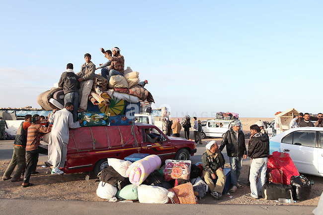 Egyptians, who have fled from Libya through the Salloum land port gate wait with their luggage,Tuesday, Feb. 22, 2011. An estimated 5,000 Egyptians have returned home from Libya by land, and about 10,000 more are waiting to cross the Libya-Egypt border, an Egyptian security official said. Egypt says it will also send six commercial and two military planes to repatriate thousands more caught in the revolt against Moammar Gadhafi's regime. Photo by Karam Nasser