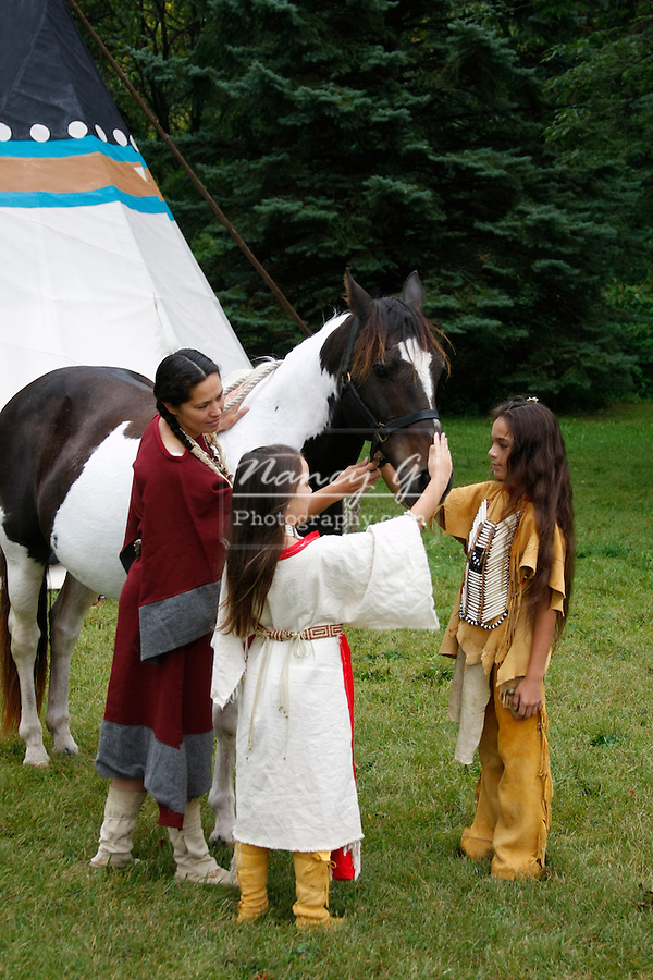 A Native American Indian family with their paint horse next to a tipi