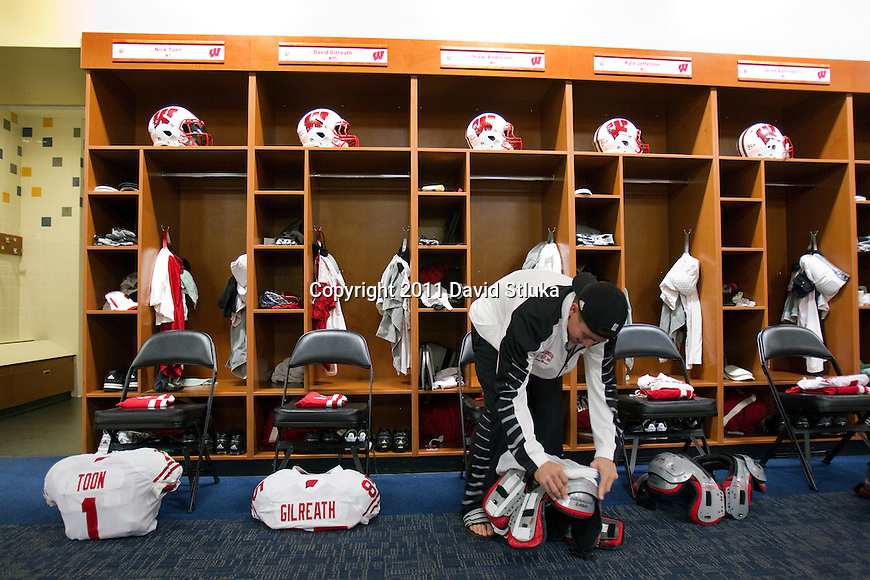 Wisconsin Badgers student manager Brett Arnold puts the jersey of wide receiver Isaac Anderson (6) on the shoulder pads prior to the 2011 Rose Bowl NCAA Football game against the TCU Horned Frogs in Pasadena, California on January 1, 2011. (Photo by David Stluka)