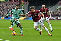Aaron Cresswell of West Ham United tackles Ainsley Maitland-Niles of Arsenal during West Ham United vs Arsenal, Premier League Football at The London Stadium on 12th January 2019