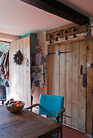 Doors throughout the restored Victorian farmhouse have been constructed using traditional tongue and groove with two examples seen in the kitchen