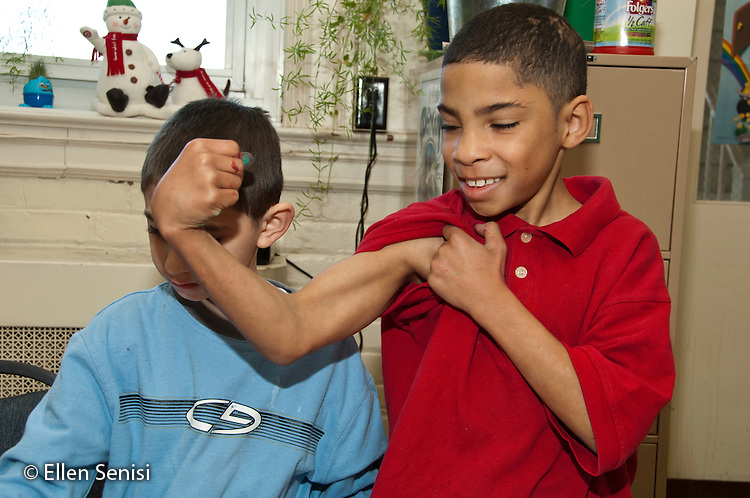 MR / Schenectady, New York. Elmer Avenue School (urban public school). 3rd grade classroom. Student (boy, age 8, African-American / Puerto Rican-American) showing off his muscles. student (boy, age 9, ADHD) in background. MR: Ree1, Cla21. ID: AH-FRD. ©Ellen B. Senisi.