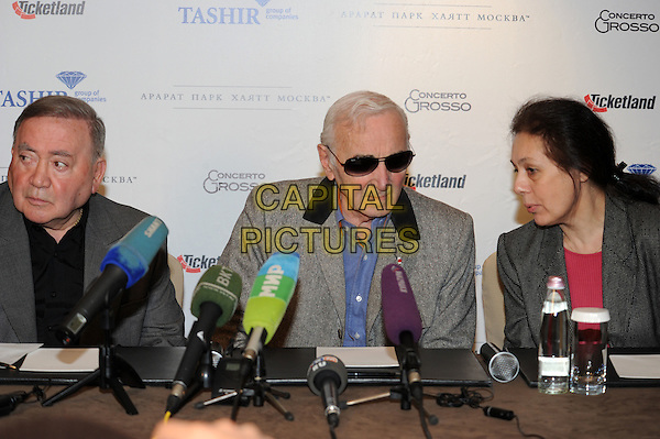 Charles Aznavour.press conference in Moscow, Russia..December 10th, 2011.half length table sitting blue shirt grey gray sunglasses shades .CAP/PER/AL.©AL/PersonaStars/CapitalPictures