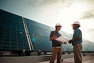 Two working discussing the installation of solar panels together.