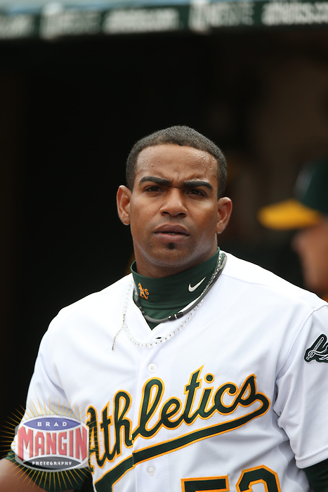 OAKLAND, CA - APRIL 2:  Yoenis Cespedes #52 of the Oakland Athletics stands in the dugout against the Cleveland Indians during the game at O.co Coliseum on Wednesday, April 2, 2014 in Oakland, California. Photo by Brad Mangin