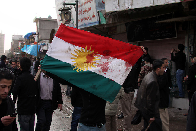 SULAIMANIYAH, IRAQ:  A man walks through the streets with a Kurdish flag stained with blood...Tension continues to grow in the semi-autonomous region of Iraqi Kurdistan as protesters clash with police on a 5th day of unrest...Photo by Haedar Omar