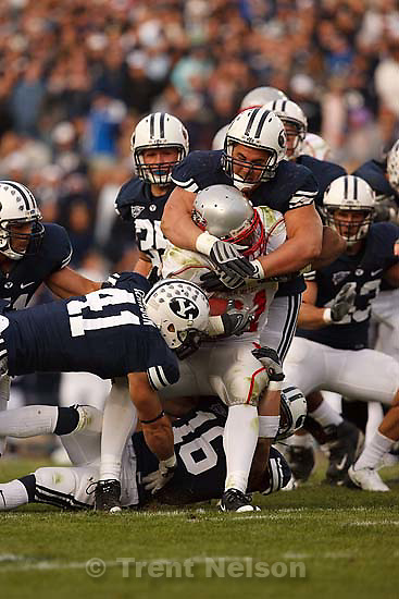 Provo - BYU DL Russell Tialavea (52, top) pulls down New Mexico's Rodney Furguson with help from BYU LB Coleby Clawson (41, lower left) and BYU DB Kellen Fowler (16, bottom). BYU vs. New Mexico college football at LaVell Edwards Stadium, Saturday, October 11, 2008.