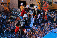 Rescuers carry the body of a victim retrieved from the rubble of the site of a garment factory that collapsed in Savar, near Dhaka, Bangladesh, Saturday, May 11, 2013.