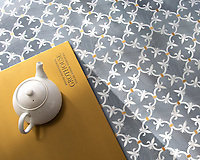 Fleur de Lys, a waterjet stone mosaic, shown in polished Bardiglio, Calacatta Gold, and Brass, is part of the Jardins Fran&ccedil;ais&trade; collection by Caroline Beaupere for New Ravenna.<br />