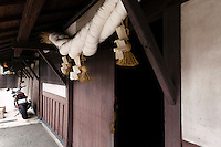 "Shinto paper and straw ropes at the entrance to the Tsukinokatsura sake brewery, Fushimi, Kyoto, Japan, October 10, 2015. Tsukinokatsura Sake Brewery was founded in 1675 and has been run by 14 generations of the Masuda family. Based in the famous sake brewing region of Fushimi, Kyoto, it has a claim to be the first sake brewery ever to produce ""nigori"" cloudy sake. It also brews and sells the oldest ""koshu"" matured sake in Japan."