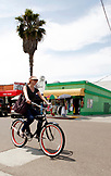 USA, California, San Diego, woman riding her bicycle through Pacific Beach