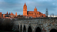 Low angle general view, Cathedral, Salamanca, Spain, pictured on December 19, 2010 lit by the evening sun with the Roman bridge in the foreground. Salamanca, Spain's most important University city,  has two adjoining Cathedrals, Old and New. The old Romanesque Cathedral was begun in the 12th century, and the new in the 16th century. Its style was designed to be Gothic rather than Renaissance in keeping with its older neighbour, but building continued over several centuries and a Baroque cupola was added in the 18th century. Restoration was necessary after the great Lisbon earthquake, 1755. Picture by Manuel Cohen
