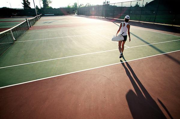 Woman tennis player walking toward courts.