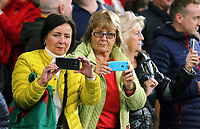 Female Wales supporters take pictures on their mobile phones during the FIFA World Cup Qualifier Group D match between Wales and Republic of Ireland at The Cardiff City Stadium, Wales, UK. Monday 09 October 2017
