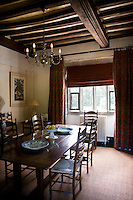 All the ceilings in the house are supported by massive oak beams, seen here lending an air of grandeur to the dinng room