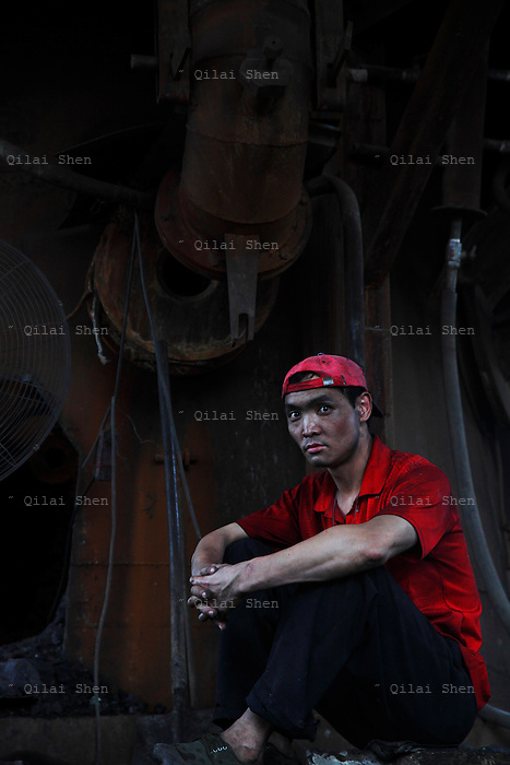 Workers take a break from doing maintenance work on equipment at the Yuanhua Smelter in Daoxian County, Hunan Province, China, on 03 June, 2010. The company makes manganese alloys and additives that are widely used in the steel industry.