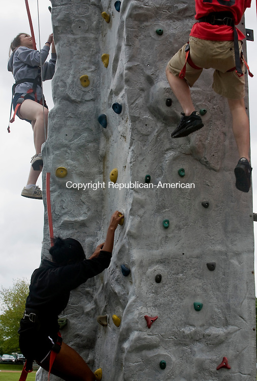 CHESHIRE--22 May 08--052208TJ03 - Cheshire High School students Christina Toth, 17, from left, Alex Tyson, 16, and Chris Baker, 17, traverse a rock wall provided by McDonald's through the company's Active Achievers program, which according to a company representative promotes a balanced and active lifestyle, on Thursday, May 22, 2008. (T.J. Kirkpatrick/Republican-American)