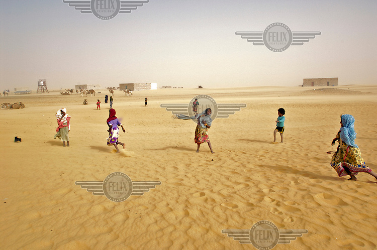 Children play in the sand in the Sahara Desrt village of Boujbeja. /Felix Features