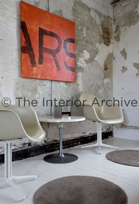 A pair of Eames chairs beneath an orange canvas which is mounted on a distressed concrete wall