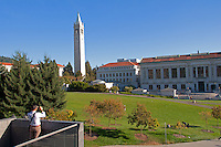 A clear day in the fall at the University of California campus in Berkeley, California. A man takes a picture at the Memorial Glade, Sather Tower, and Doe Memorial Library.