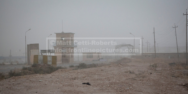 28/09/2014. Rabia, Iraq. A sandstorm moves in to hamper visibility at the Iraq-Syria border crossing towns of Al-Yarubiyah, Syria, and Rabia, Iraq.<br /> <br /> Facing each other across the Iraq-Syria border, the towns of Al-Yarubiyah, Syria, and Rabia, Iraq, were taken by Islamic State insurgents in August 2014. Since then The town of Al-Yarubiyah and parts of Rabia have been re-taken by fighters from the Syrian Kurdish YPG. At present the situation in the towns is static, but with large exchanges of sniper and heavy machine gun fire as well as mortars and rocket propelled grenades, recently occasional close quarter fighting has taken place as either side tests the defences of the other.