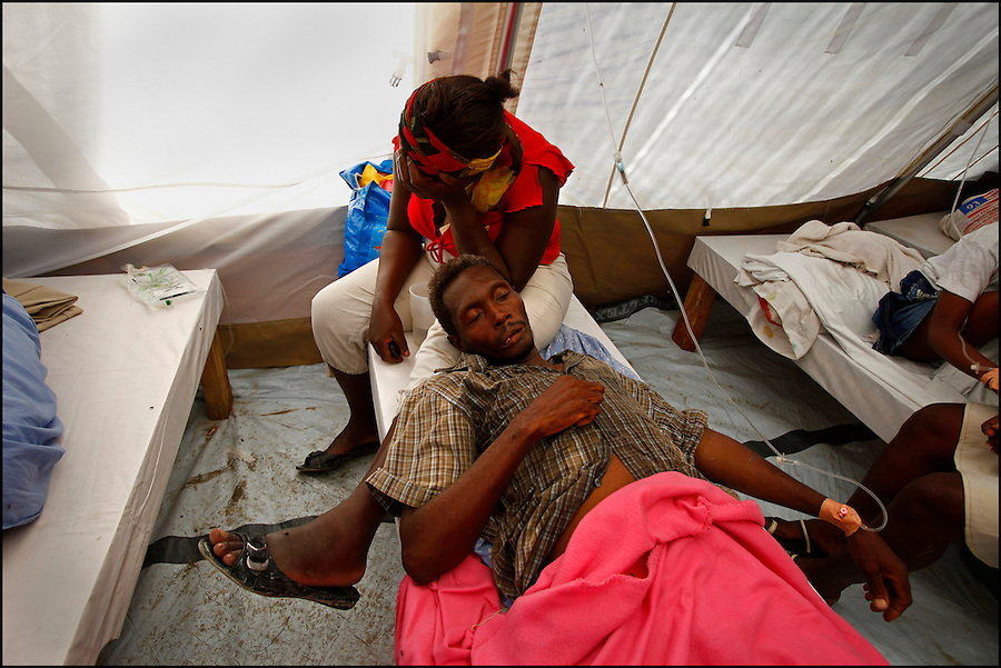 Nov 10, 2010 - Port-au-Prince, Haiti.A local resident looks after a family member suffering from cholera-like symptoms as he receives medical treatment in a small, crowded medical clinic set up in tents in the Cite Soleil area of Port-au-Prince, Haiti, Wednesday, November 10, 2010 as fears of a cholera outbreak spread through the area just two days after cases of the infection were confirmed in the area, the poorest slum in Haiti's capital. Officials from the Pan American Health Organization warn that Haiti's cholera epidemic, spread primarily through consuming infected water and food, is likely to grow much larger in the wake of Hurricane Tomas.  (Credit Image: Brian Blanco)