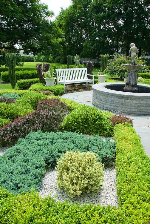 Knot garden, Buxus, Juniper, Berberis, patio. water fountain, bench, beautiful home backyard landscaping with lawn area, trees, shrubs, containers, in classic style