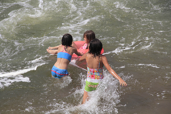 Three girls playing in an inner tube in whitewater, Denver, Colorado, USA.