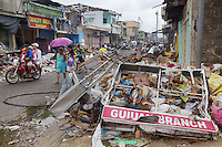 Philippines. Province Eastern Samar. Guiuan. A family of four persons (father, mother, son and daughter) rides a motorcycle on the road. A Guiuan Branch bank sign with rubble and garbage on the ground. A grandmother and her granddaughtes walks with a purple umbrella in the street cleared of debris. The Quality Bread bakeshop hat reopen the shop.The 300 kph (or km/h) winds of typhoon Haiyan has blown and destroyed houses, ripped rooftops apart and smashed walls. The town of Guiuan was the first to face the fury of typhoon Haiyan when it barrelled into the Philippines on november 8 2013. Typhoon Haiyan, known as Typhoon Yolanda in the Philippines, was an exceptionally powerful tropical cyclone that devastated the country. Haiyan is also the strongest storm recorded at landfall in terms of wind speed (300 km per hour). 28.11.13 © 2013 Didier Ruef