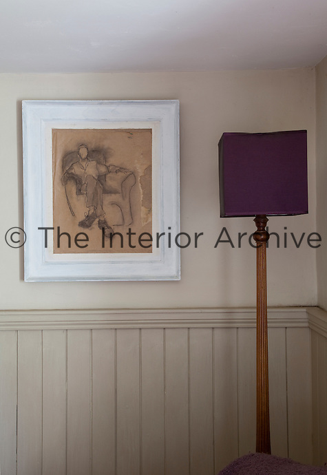 A framed drawing hangs on the wall of the living room next to a floor lamp with a purple shade