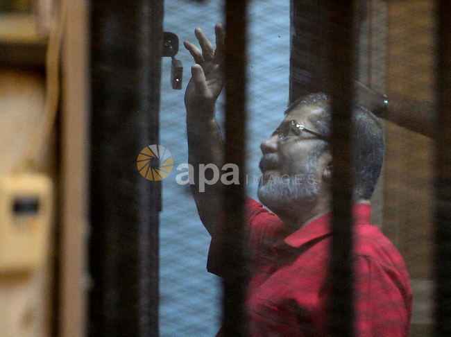 Ousted Egyptian president Mohammed Morsi waves as he stands behind bars during his trail in a court in Cairo on August 30, 2015. Cairo criminal court resumes today the trial of deposed president Mohamed Morsi and 10 others on charges of espionage and leaking classified documents related to the national security and the army to Qatar. Photo by Amr Sayed
