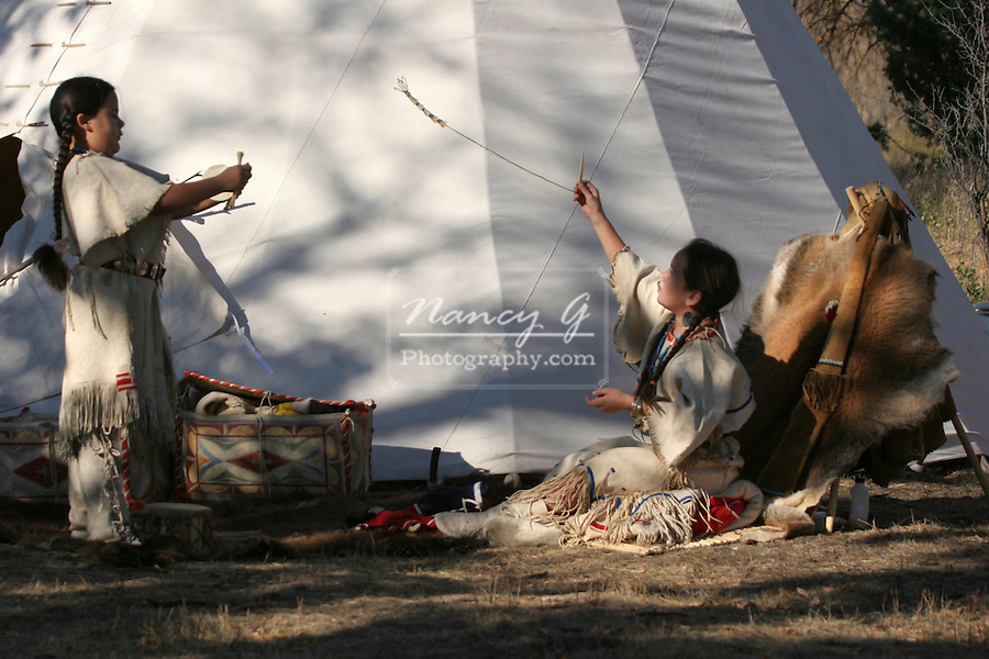 Two Native American Indian children playing with native American toys with string, beads and bones