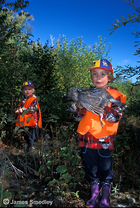 Young girl hunters holding shot ruffed grouse