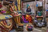 """Brothel, Mumbai, India 2018<br /> These three women share a room in the red light district where they live and work. Sarita has lived in this brothel for 20 years, working as a sex worker. One of her regular customers became her """"husband,"""" a common practice among sex workers here in which women are dedicated only to individual men. Anju also lives here as a sex worker, and Parvati lives under her bed. Parvati has two sons, both drug addicts, and she works in this industry to support them. Many women who end up here have been sold by husbands or hustlers, drugged, or tricked with the promise of a legitimate job. These women make a couple of dollars per client, often sending whatever money they make home to support their families. Their names have been changed for their protection."""