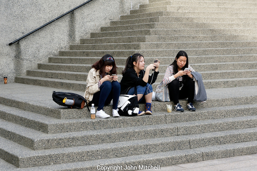 Three young Asian women sitting on concrete steps using their smart phones, Vancouver, BC, Canada