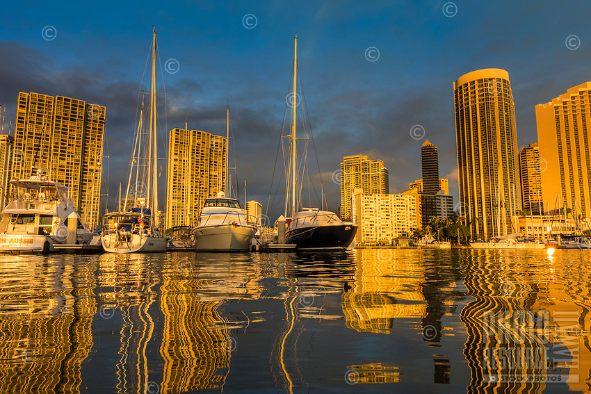 At sunset, boats and buildings reflect in the calm water at Waikiki Yacht Club, Honolulu, O'ahu.