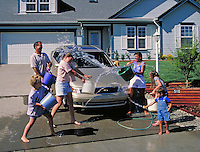 family having fun and throwing water while washing car in suburban neighborhood. family.